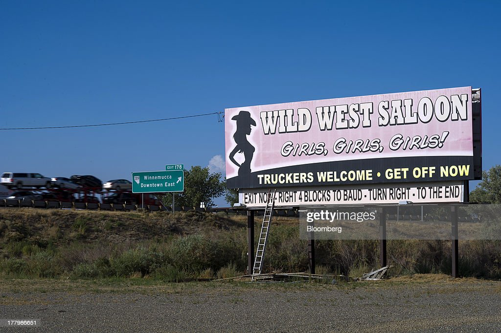 A billboard is displayed outside the Wild West Saloon & Brothel in Winnemucca, Nevada, U.S., on Wednesday, Aug. 21, 2013. Growing use of the Internet to arrange liaisons with prostitutes and decreased patronage by truckers squeezed by rising fuel costs are also hurting houses of prostitution that took root during Nevada's mid-1800s silver-mining boom, George Flint, lobbyist for the Nevada Brothel Owners Association and brothel managers say. Photographer: David Paul Morris/Bloomberg via Getty Images