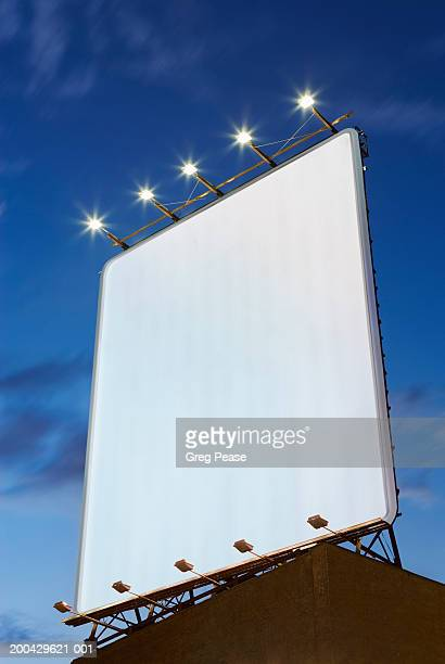 billboard on rooftop, low angle view, dusk - vertikal stock-fotos und bilder