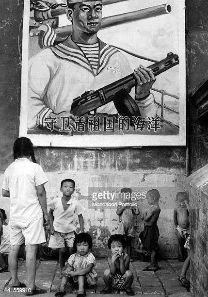 A billboard propaganda rising above some children in a street of the capital Beijing 1961