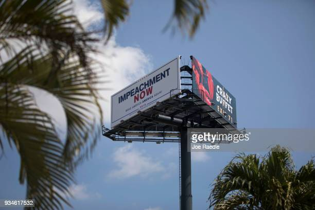 A billboard reading 'Impeachment Now Make America America Again' calling for President Donald Trump's impeachment is seen along a street leading to...