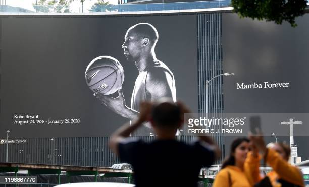 A billboard salutes the life of Kobe Bryant as fans gather outside Staples Center to mourn the death of NBA legend Kobe Bryant at a mural near...