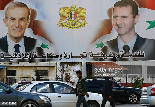 A billboard sponsored by Latakia's chamber of commerce and industry shows pictures of Syrian President Bashar alAssad and his late father former...