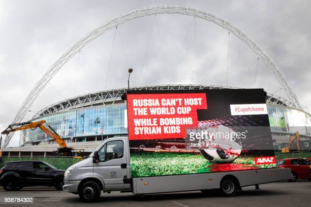 A billboard truck with the words 'Russia Can't Host the World Cup While Bombing Syrian Kids' and an image of a bloodied football drives past Wembley...