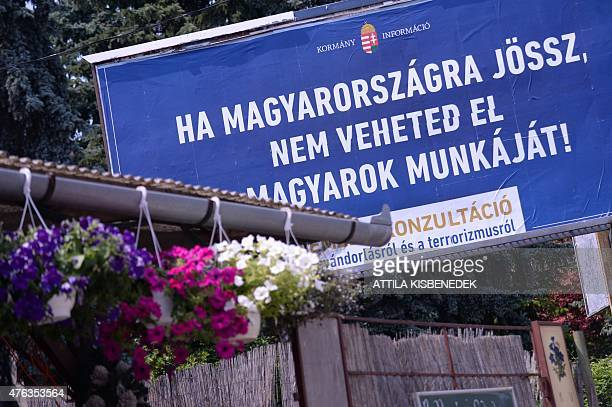 A billboard with a statefunded antiimmigration poster reads in Hungarian 'If you come to Hungary do not take the Hungarians' jobs ' at the third...