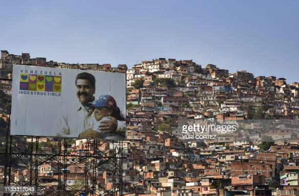 TOPSHOT A billboard with an image of Venezuela's President Nicolas Maduro embracing his wife Cilia Flores and a legend reading Indestructible...