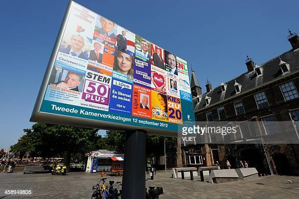 billboard with election posters in the hague - verkiezing stockfoto's en -beelden