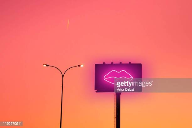 billboard with sexy lips neon light and sunset sky in the city. - image stock pictures, royalty-free photos & images