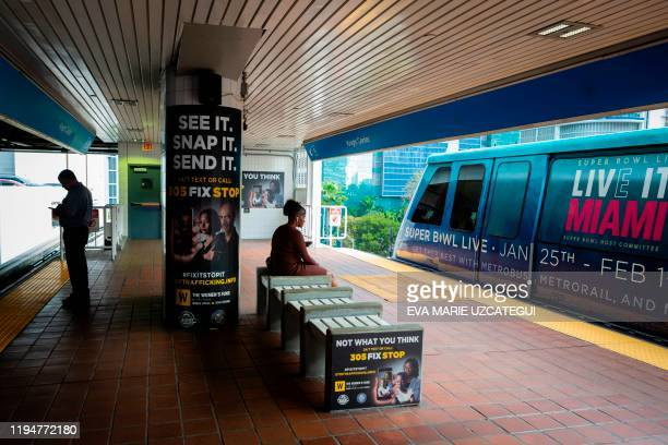 Billboards displaying a campaign against human trafficking are seen at Knight Center Metrorail station as a train depicting the Super Bowl logo...