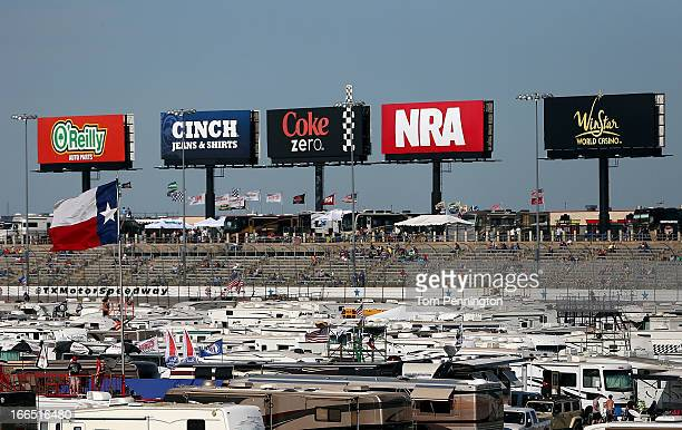 Billboards for O'Riely Auto Parts Cinch Jeans Shorts COke Zero the NRA and Winstar World Casino are displayed above campers parked on the infield and...