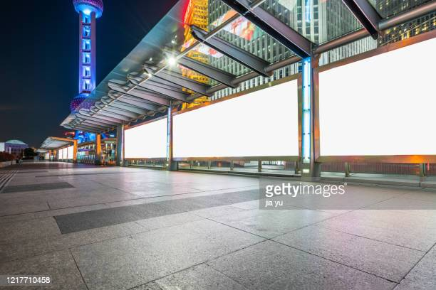 billboards on sidewalks in lujiazui financial district, pudong, shanghai. night. - famous place stock pictures, royalty-free photos & images