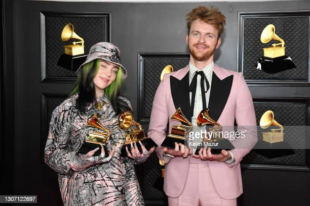 """Billie Eilish and FINNEAS, winners of Record of the Year for 'Everything I Wanted' and Best Song Written For Visual Media for """"No Time To Die"""", pose..."""