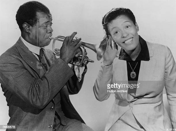 Billie Holiday pays close attention to Louis Armstrong . They are both appearing in the film, 'New Orleans' directed by Arthur Lubin.