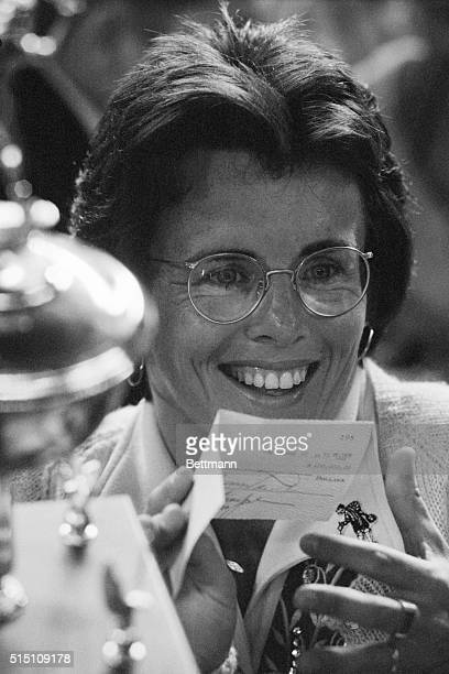 Billie Jean King holds up her trophy and a check for $100000 after winning the 'Battle of the Sexes' against aging tennis hustler Bobby Riggs at the...