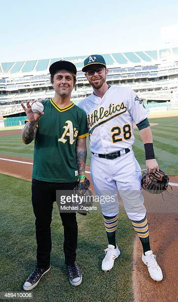 Billie Joe Armstrong of Green Day and Eric Sogard of the Oakland Athletics stand on the field prior to the game between the Athletics and the Seattle...