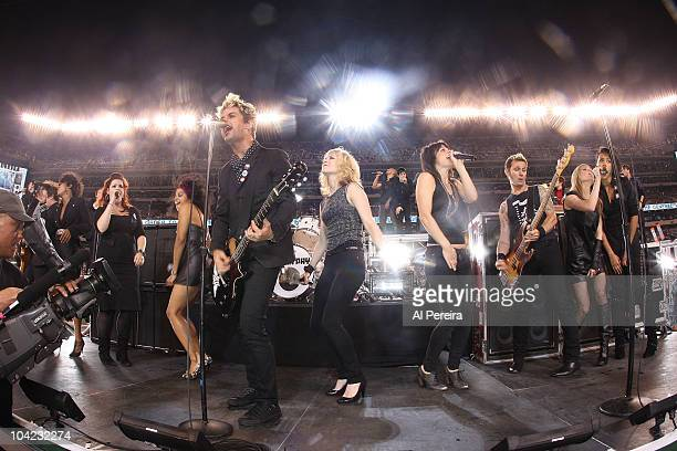 Billie Joe Armstrong of Green Day are joined by the cast of 'American Idiot' on stage when they perform at the New York Jet's 2010 opening game at...