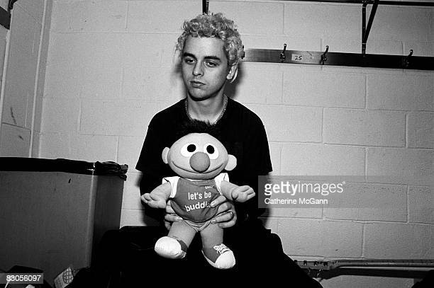 Billie Joe Armstrong of Green Day poses for a portrait holding a stuffed doll of Ernie from Sesame Street printed with the words Let's Be Buddies...