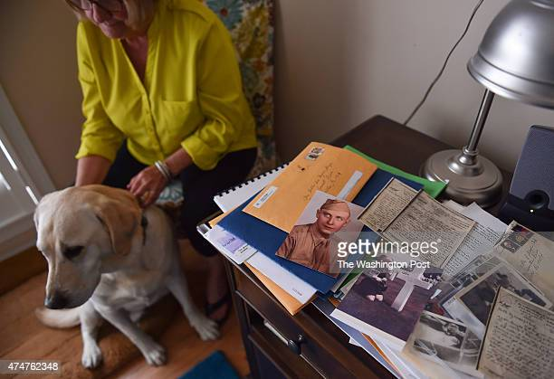 Billie Meeks is photographed in her home with her yellow lab named Dyson as old letters and photos from her father's service in WWII are seen on a...