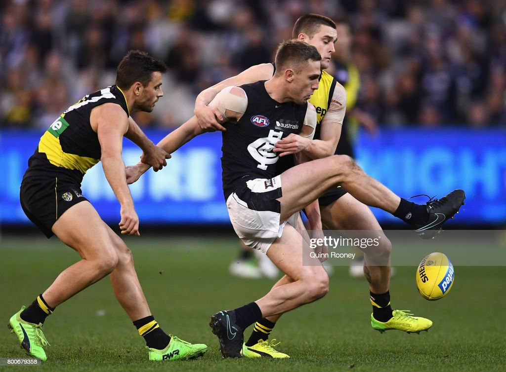 Billie Smedts of the Blues kicks whilst being tackled by Sam Lloyd and Jayden Short of the Tigers during the round 14 AFL match between the Richmond Tigers and the Carlton Blues at Melbourne Cricket Ground on June 25, 2017 in Melbourne, Australia.