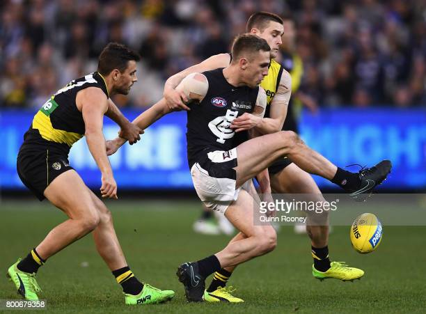 Billie Smedts of the Blues kicks whilst being tackled by Sam Lloyd and Jayden Short of the Tigers during the round 14 AFL match between the Richmond...