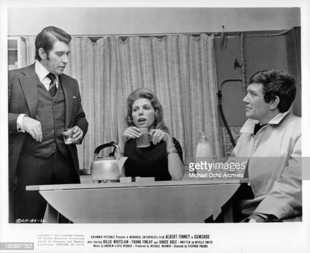 Billie Whitelaw and Albert Finney sitting at a table with an unknown actor standing in a scene from the film 'Gumshoe', 1971.