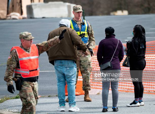 A member of the military police with the Maryland National guard stops people that wanted to be tested for coronavirus from entering a mobile testing...