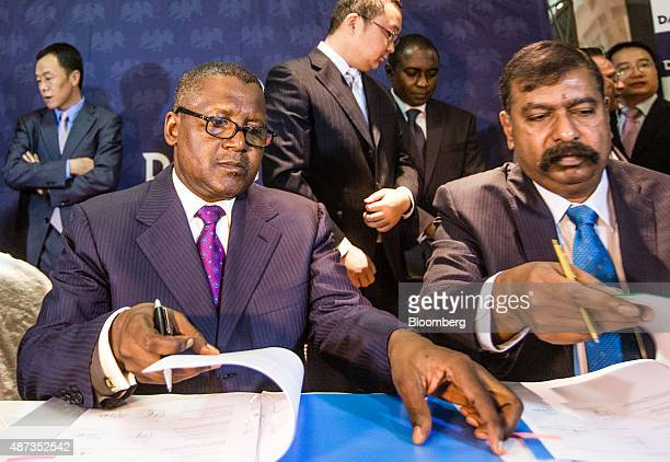 Billionaire Aliko Dangote chief executive officer of Dangote Group left turns a page to sign a factory construction contract with Sinoma...