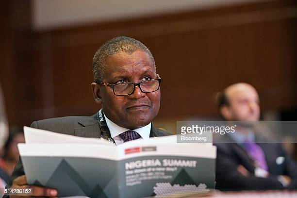 Billionaire Aliko Dangote president and chief executive officer of Dangote Group holds a conference brochure while taking part in The Economist...