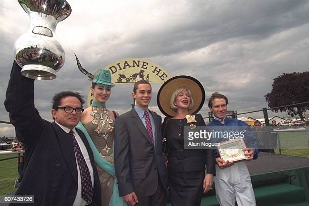 Billionaire art dealer Alec Wildenstein raises the trophy after his horse Aquarelliste won the Prix de Diane at Chantilly Racecourse Chantilly Oise...