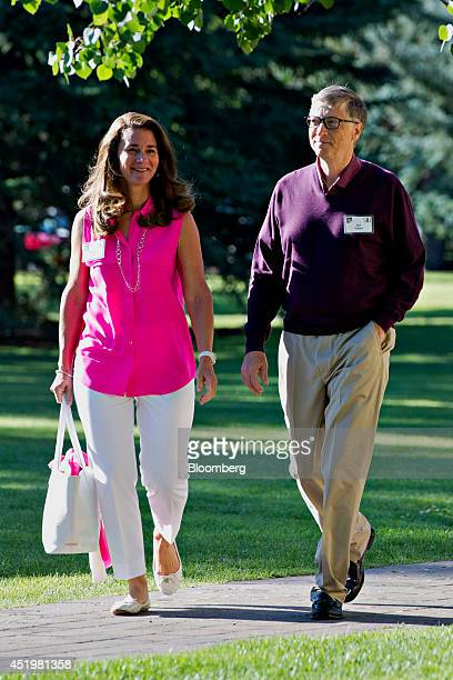 Billionaire Bill Gates chairman and founder of Microsoft Corp right walks with his wife Melinda Gates as they arrive for a morning session during the...