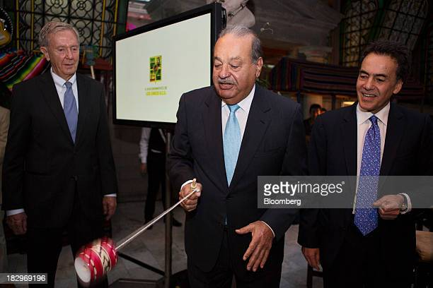 Billionaire Carlos Slim center plays with a traditional balero cupandball toy as Omar Vidal director of World Wildlife Fund Mexico right and Bruce...