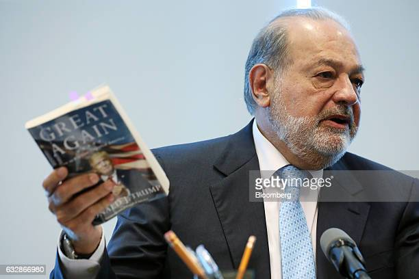 Billionaire Carlos Slim chairman emeritus of America Movil SAB and Telefonos de Mexico SAB speaks while holding up US President Donald Trump's book...