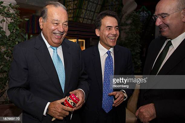 Billionaire Carlos Slim left reacts while holding a traditional balero cupandball toy as Omar Vidal director of World Wildlife Fund Mexico center...