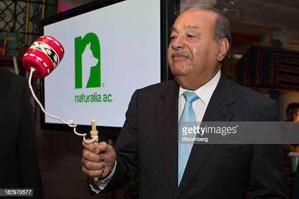 Billionaire Carlos Slim plays with a traditional balero cupandball toy during an event to announce an alliance between his philanthropic foundation...