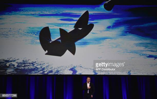 Billionaire entrepreneur and founder of SpaceX Elon Musk speaks below a computer generated illustration of his new rocket at the 68th International...
