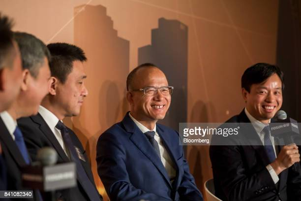 Billionaire Guo Guangchang chairman and cofounder of Fosun International Ltd second right reacts as Wang Qunbin chief executive officer right speaks...