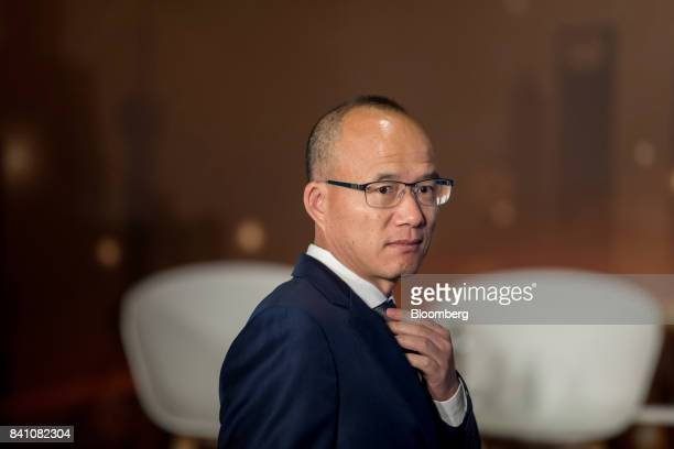 Billionaire Guo Guangchang chairman and cofounder of Fosun International Ltd adjusts his tie as he arrives at a news conference in Hong Kong China on...