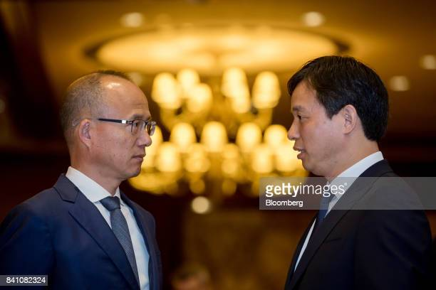 Billionaire Guo Guangchang chairman and cofounder of Fosun International Ltd left looks at Wang Qunbin chief executive officer as they pose for a...