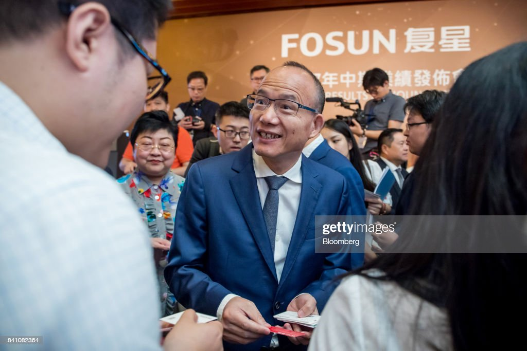 Billionaire Guo Guangchang, chairman and co-founder of Fosun International Ltd., center, speaks with members of the media following a news conference in Hong Kong, China, on Thursday, Aug. 31, 2017. Fosun the listed flagship ofGuo's insurance-to-drugs conglomerate, reported first-half net income increased 34 percent amid higher returns from investments. Photographer: Paul Yeung/Bloomberg via Getty Images