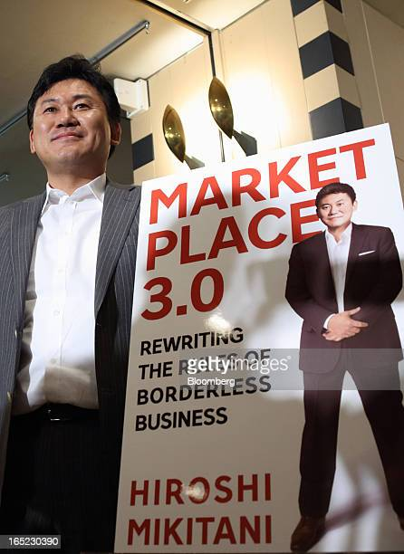 Billionaire Hiroshi Mikitani chairman and chief executive officer of Rakuten Inc poses with a promotional poster of his book at the Foreign...