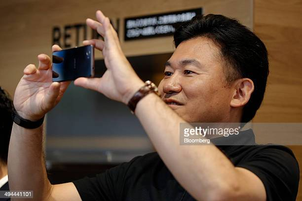 Billionaire Hiroshi Mikitani chairman and chief executive officer of Rakuten Inc uses a smartphone to take photographs during the opening of the...