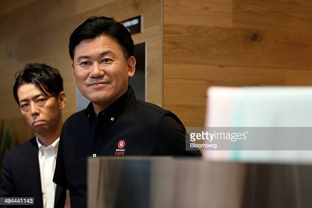 Billionaire Hiroshi Mikitani chairman and chief executive officer of Rakuten Inc right smiles during the opening of the company's Rakuten Cafe in...