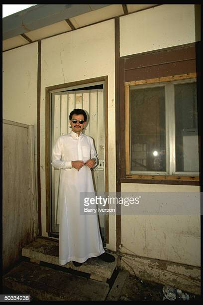 Billionaire investor Saudi Prince Alwaleed standing in doorway of his palace bedroom