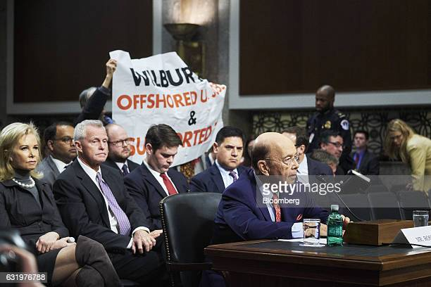 Billionaire investor Wilbur Ross commerce secretary nominee for US Presidentelect Donald Trump pauses as protesters hold up a sign during a Senate...