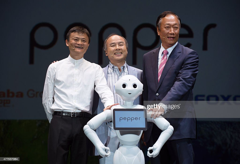Billionaire Jack Ma, chairman of Alibaba Group Holding Ltd., left, billionaire Masayoshi Son, chairman and chief executive officer of SoftBank Corp., center, and billionaire Terry Gou, chairman of Hon Hai Precision Industry Co., pose with humanoid robot Pepper during a news conference in Urayasu, Chiba Prefecture, Japan, on Thursday, June 18, 2015. SoftBank will start sales of its Pepper robot to consumers Saturday in a bid to spur adoption. Photographer: Akio Kon/Bloomberg via Getty Images