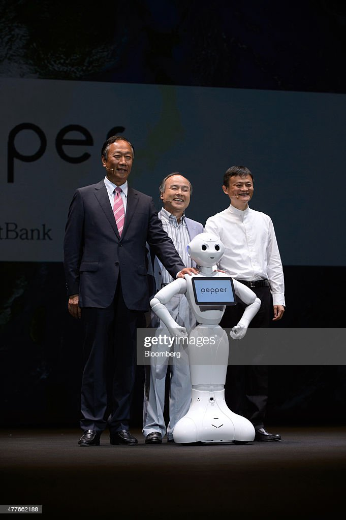 Billionaire Jack Ma, chairman of Alibaba Group Holding Ltd., left, billionaire Masayoshi Son, chairman and chief executive officer of SoftBank Corp., center, and billionaire Terry Gou, chairman of Hon Hai Precision Industry Co., poses for a photograph with humanoid robot Pepper during a news conference in Urayasu, Chiba Prefecture, Japan, on Thursday, June 18, 2015. SoftBank will start sales of its Pepper robot to consumers Saturday in a bid to spur adoption. Photographer: Akio Kon/Bloomberg via Getty Images