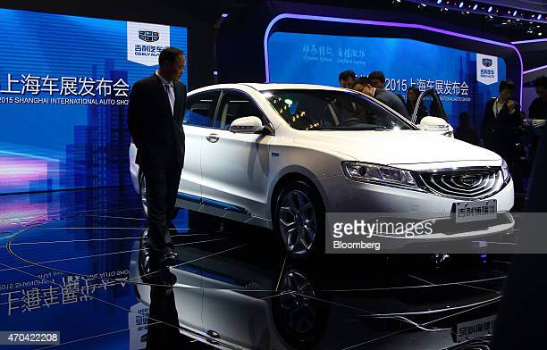 Billionaire Li Shufu founder and chairman of Geely Automobile Holdings Ltd left looks at the company's GC9 sedan displayed at the 16th Shanghai...