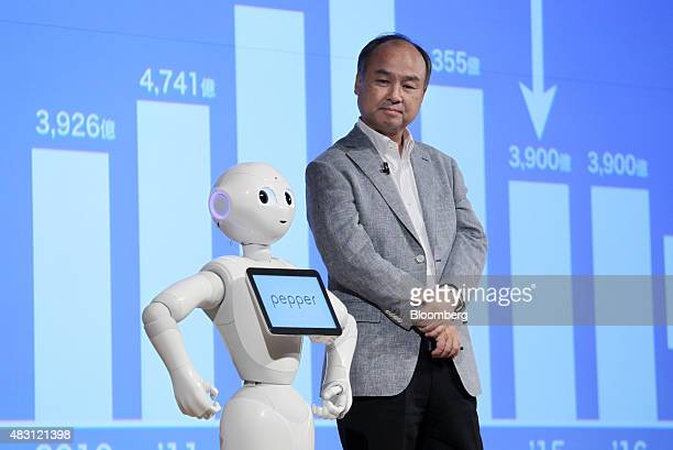Billionaire Masayoshi Son, chairman and chief executive officer of SoftBank Group Corp., right, looks on as the company's humanoid robot Pepper...