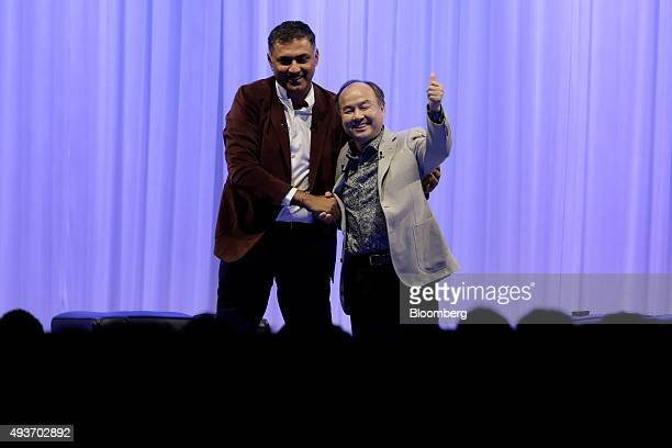 Billionaire Masayoshi Son chairman and chief executive officer of SoftBank Group Corp right gestures as he shakes hands with Nikesh Arora president...