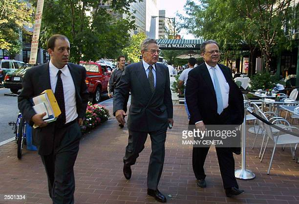 Billionaire philanthropist George Soros walks with unidentified officials of the Open Society Institute in Washington DC 16 September 2003 AFP...