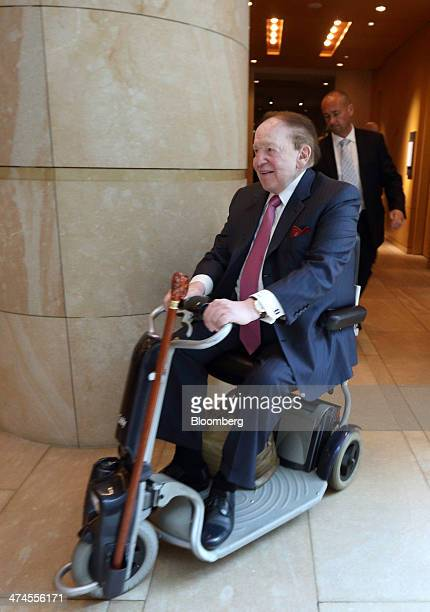 Billionaire Sheldon Adelson chairman and chief executive officer of Las Vegas Sands Corp rides a mobility scooter as he leaves a news conference at...